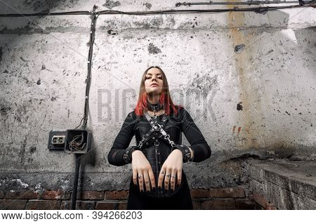 Sexy Dominant Woman With Piercings And Bright Hair In A Black Corset, With Leather Harnesses And Bra