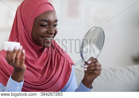 Home Beauty Treatment. Young Black Muslim Lady In Hijab Holding Jar With Moisturising Cream And Look