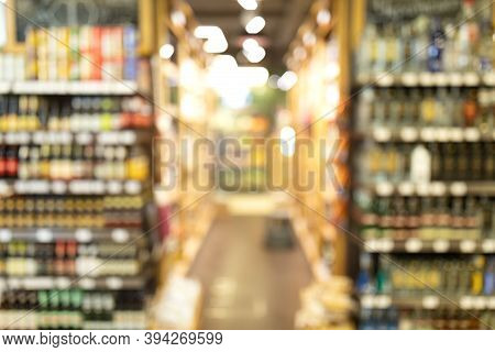 Shelves With Alcohol Drinks In Supermarket, Abstract Blurred Background. Grocery Store Aisle With Va