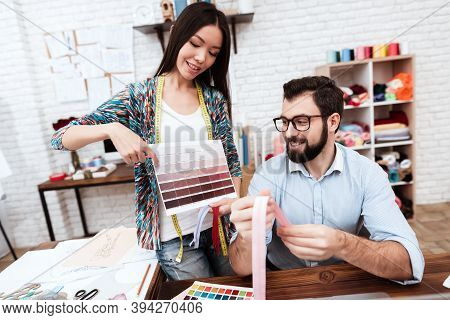 Two Male And Female Fashion Designers Looking At Color Swatches. Designer Girl Offers Her Color For