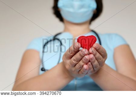 Saving Lives During A Covid-19 Coronavirus Pandemic, Woman Doctor In Medical Mask Holding Red Knitte
