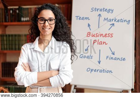 Presentation And Brainstorming Concept. Portrait Of Confident Businesswoman In Eyeglasses Posing Nea