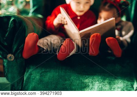 Brother And Sister Are Sitting On A Green Armchair And Reading A Book. Christmas Mood. Children In N