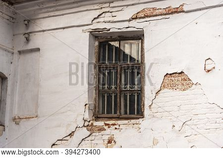 Abandoned Or Neglected House With Damaged Dirty Brick Walls And Window Glass. Weathered Dwelling In