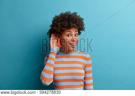 Eavesdropping And Gossiping Concept. Curious Cheerful Woman Holds Hand Near Ear And Tries To Hear In