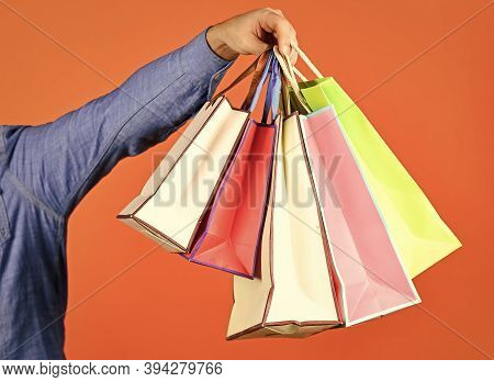 Hand Hold Bags. Shopping Bags In Hand On Red Background. Paper Bags Different Colors. Shopping In Ma