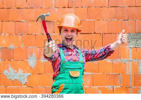 Cheerful Child Laborer Using Building Uniform And Hammer Tool, Laborer
