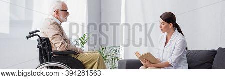 Worker Reading Book To Elderly Man In Wheelchair, Banner