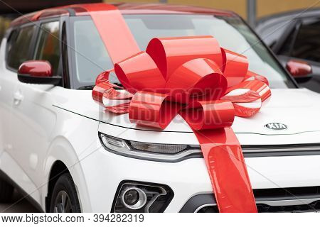White Kia Car With A Big Red Bow On The Street, Sale In The Kia Showroom, New Car For A New Owner Su