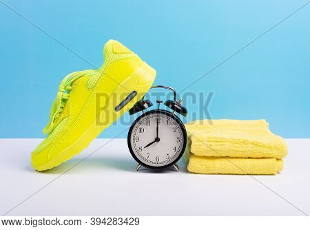 Marathon Running Concept With Sport Shoe, Towel And Alarm Clock Over Blue Wall Background. Fitness,