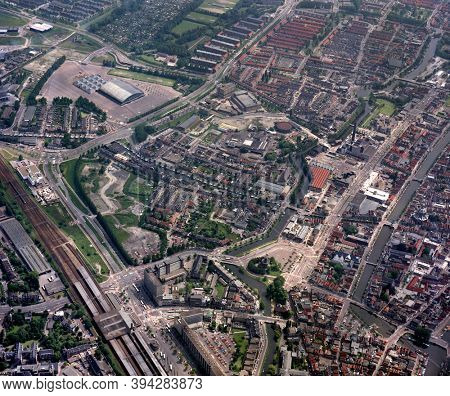 Leiden, Holland, June 17- 1985: Historical aerial photo of the Station neighbourhood with windmill the Valk, Groenoordhallen and Central Station