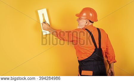 Plastering Tools For Plaster. Plaster Trowel Spatula On Yellow Drywall Plasterboard. Plasterer In Wo