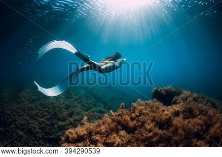 Freediver Girl With White Fins Glides Near Rock With Seaweed And Sun Rays. Freediving And Beautiful