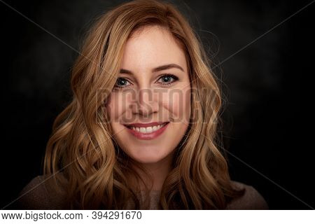 Portrait Of A Young Blonde Woman On A Dark Background.