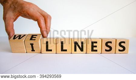 Wellness Or Illness. Male Hand Flips Wooden Cubes And Changes The Inscription 'illness' To 'wellness