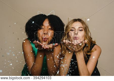 Black And Caucasian Beautiful Young Women Blowing Confetti Into The Camera On A Beige Background. Ce