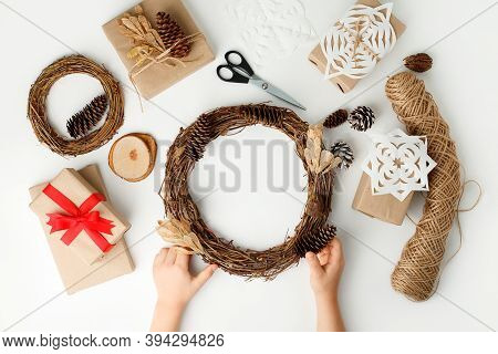 Child's Hands Making Christmas Wreath. Flat Lay, Top View, Kid Hands Wrapped Gift Box In Craft Paper