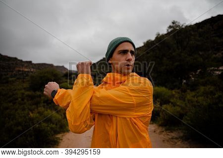 Focused Young Male Hiker Stretching Shoulder Muscle After Steep Hike Up Mountain Trail In Cloudy Wea