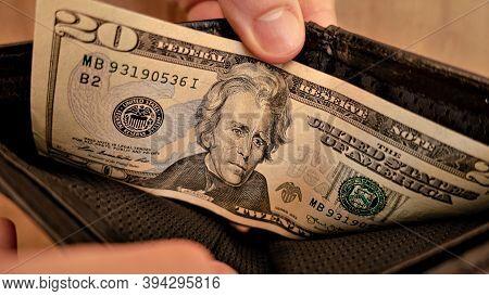 A Twenty Dollar Bill In A Black Wallet. Human Hands Open The Wallet.
