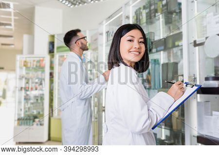 Asian Pharmacist In White Coat Writing On Clipboard Near Colleague On Blurred Background
