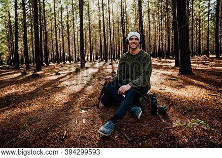 Caucasian Male Listening To Music Wearing Headphones Choosing Songs On Smartphone Relaxing In Luscio