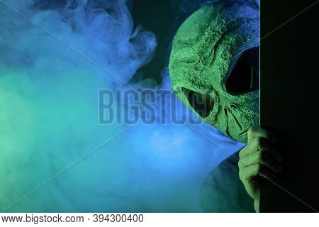 Alien Is Hiding In The Smoke On Dark Background.