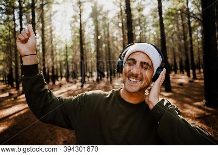 Caucasian Male Teenager Dancing Freely While Listening To Music Wearing Headphones In Luscious Woodl