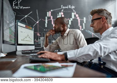 Two Diverse Colleagues Traders Talking To Each Other, Looking At Graphs While Sitting In The Office