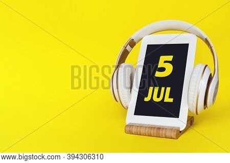 July 5th. Day 5 Of Month, Calendar Date. Stylish Headphones And Modern Tablet On Yellow Background.