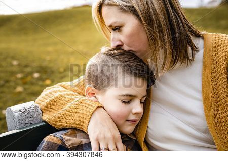 Mother Consoling Child Boy In The Autumn Leaf Fall Sit On Bench