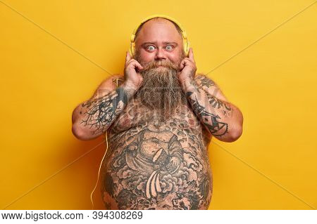 Shocked Bald Man With Naked Obese Body, Has Tattooed Arms And Belly, Thick Beard, Chills With Good V