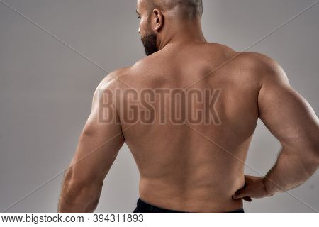 Strong And Powerful. Rear View Of Young Muscular Caucasian Bodybuilder Showing Strong Back While Sta