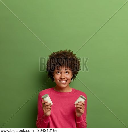Vertical Shot Of Happy Dark Skinned Woman With Afro Hair, Bites Lips, Holds Fresh Homemade Yoghurt I