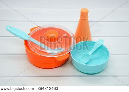 Still Life Of Children's Toy Plastic Dishes: Saucepan, Gravy Boat, Ladle, Deep Plate With Spoon. Evo