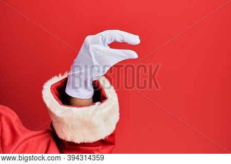 Hand of a man wearing santa claus costume and gloves over red background picking and taking invisible thing, holding object with fingers showing space