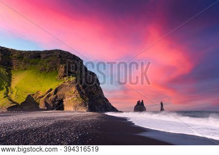 Incredible view on Black beach and Troll toes cliffs in sunset time. Great purple sky glowing on background. Reynisdrangar, Vik, Iceland. Landscape photography