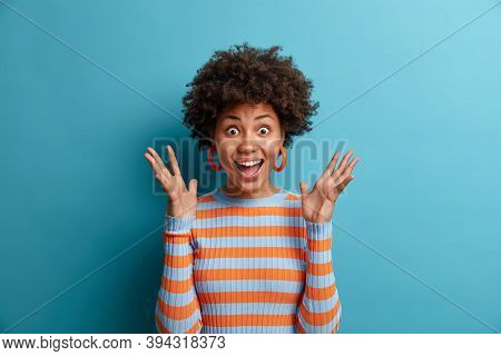 Portrait Of Delighted Cheerful Ethnic Woman Reacts On Awesome Gift, Raises Palms And Stares With Eye