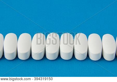 Pharmacy Concept Of White Pills On Blue Background With Copy Space