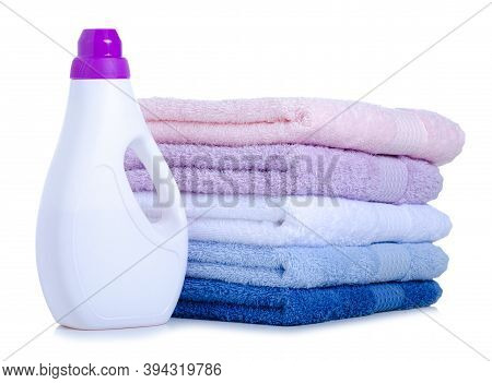 Stack Folded Towels And Liquid Detergent On White Background Isolation