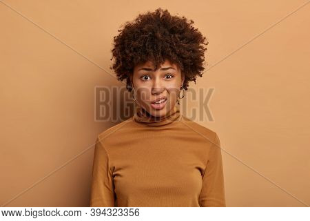 Dissatisfied Dark Skinned Young Woman Purses Lips, Looks Unpleasantly At Camera, Expresses Aversion,