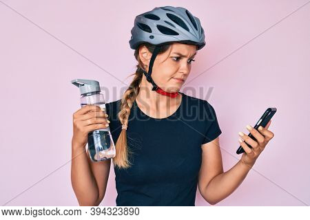 Beautiful caucasian woman wearing bike helmet looking at smartphone skeptic and nervous, frowning upset because of problem. negative person.