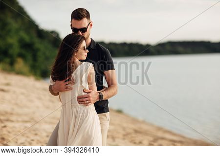 Happy Lovers At The Beach Near Lake. Young Couple Is Hugging At Sunset On Summer Day Outdoors. A Man
