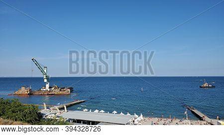 Wrecked Cargo Ship Lies On Side Near Coastline With Sandy Beach. Floating Crane Near Barrier Of Poll