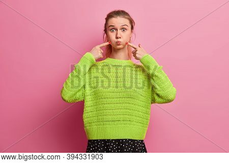 Playful Joyful European Girl Makes Funny Face, Holds Breath, Pokes Cheeks With Fingers To Blow Air,