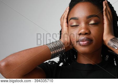 Close-up Portrait Of Young Black Woman With Curly Hair Posing In Studio. Dark-skinned Woman Wit Perf