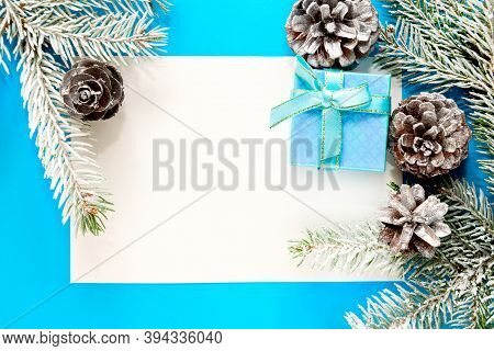 Blue Christmas Background, Frame With Fir Branches, Gift Box And Silver Decorations