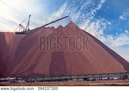Extracting And Mining Potassium Salts. Large Excavator Machine And Huge Mountains Of Waste Ore In Th