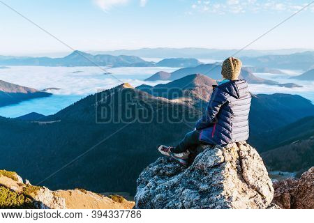 Young Hiker Woman Sitting On The Mountain Summit Cliff And Enjoying Mountains Valley Covered With Cl