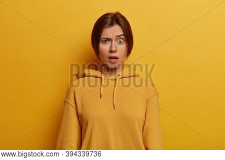 Photo Of Indignant Young European Woman Raises Eyebrows, Has Unexpected Expression, Smirks Face, Wea