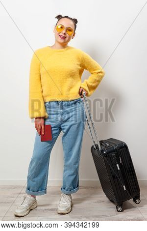 Close-up Woman Holding A Passport And Travel Bag In Her Hands. Travel, Immigration, Emigration Conce